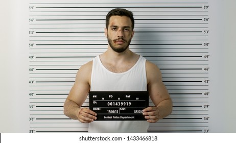 In a Police Station Arrested Beaten Man Poses for Front View Mugshot. He Wears Singlet, is Heavily Bruised and Holds Placard. Height Chart in the Background.