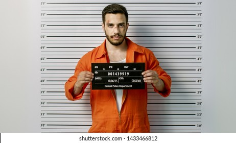 In a Police Station Arrested Man Getting Front-View Mug Shot. He's Wearing Prisoner Orange Jumpsuit and Holds Placard. Height Chart in the Background.