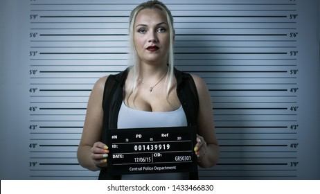 In a Police Station Arrested Woman Gets Front-View Mug Shot. She Wears Saucy Clothes, Has Heavy Makeup and Holds Placard. Height Chart in the Background. Shot with Dark Cold Lights and Vignette Filter