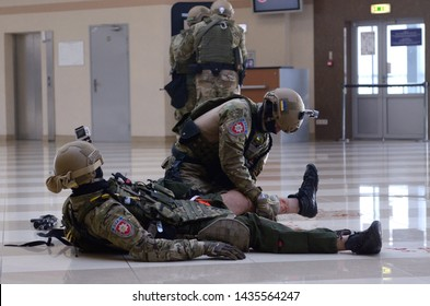 Police strike force training. Soldier of KORD (police strike force, SWAT) giving first aid to his wounded fellow, others took position. September 5, 2018. Kiev, Ukraine