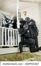 Police tactical or swat team gathered round the door of a house with drawn weapons and protective clothing simulating an arrest or hostage stand-off situation