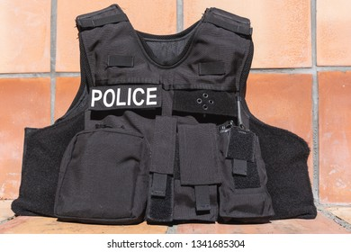 Police tactical vest with baton, radio, shears, and tourniquet