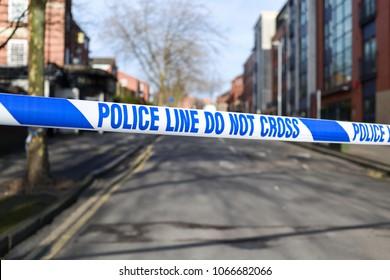 Police tape across street crime scene investigation.