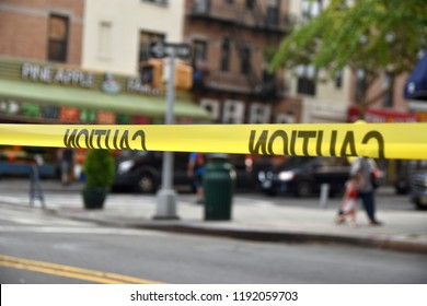 Police tape cordons off a street, with a blurred view of a Brooklyn neighborhood in the distance.