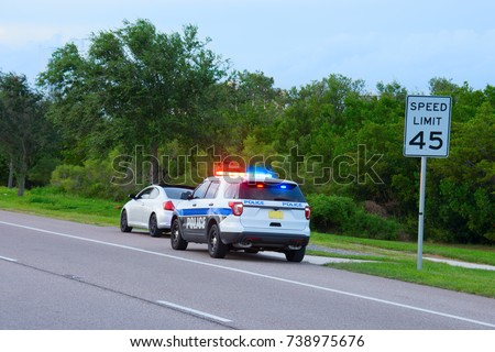 Police truck suv vehicle with flashing red and blue lights has pulled over a sports car for speeding and they happen to be on the side of the road by a speed limit sign.