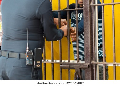 Police unlocking a handcuffs from male hand, In prison, in Thailand
