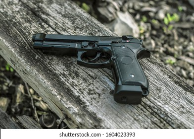 Police weapon / Beretta M9 black gun on the ground, firearm background. Metal 9mm pistol, special forces gun, military ammo. Weapons and ammunition scenery