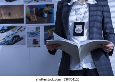 Police woman is reviewing files and documents