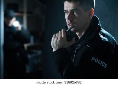 Policeman at action talking on walkie talkie