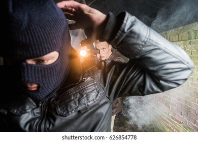 Policeman Aiming Pistol Towards Busted Gangster