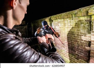 Policeman Aiming Pistol Towards Scared Cracksman At Night
