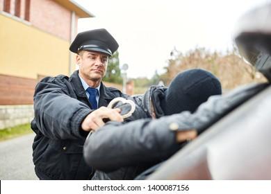 Policeman arresting burglar with handcuffs