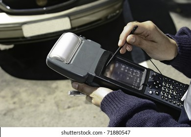 Policeman is checking cars, device for checking parking payment