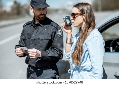 Policeman checking woman driver for alcohol intoxication with special device while stopped for violation traffic rules on the roadside