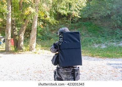 Policeman cover behind a bulletproof shield