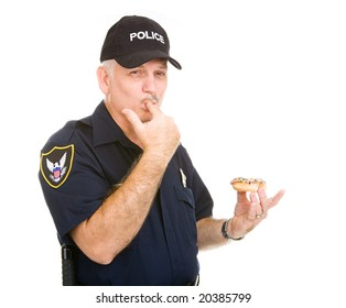 Policeman with a donut, licking icing off his fingers.  Isolated on white.