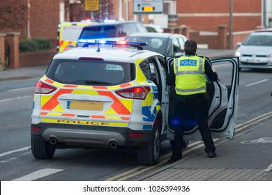 policeman entering vehicle on busy road attending a road accident