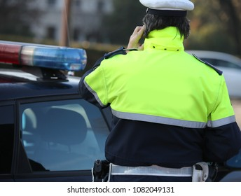 policeman in a fluorescent jacket while talking on the phone with his superior to handle an emergency