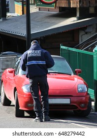 Policeman giving a parking ticket to red sports car,Chatel, French Alps,France