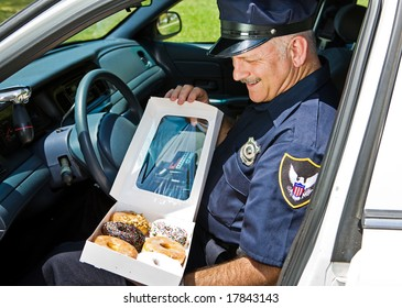 Policeman in his squad car, hungrily looking at a box of donuts.
