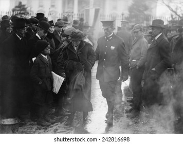 Policeman leads an arrested National Woman's Party protestor away from a woman's suffrage bonfire demonstration at the White House in 1918.