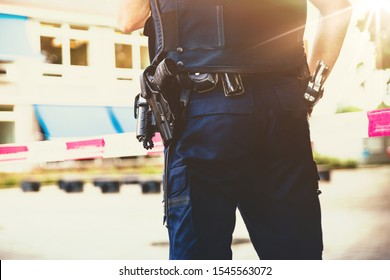 Policeman on crime scene . Red plastic tape and police officer, gun belt, handcuffs and gun