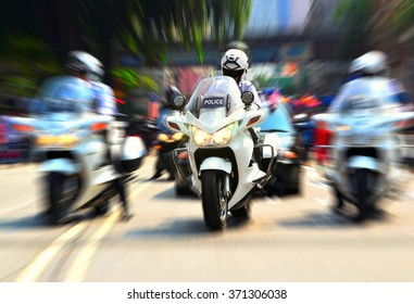 Policeman on motorcycle escorting government officials