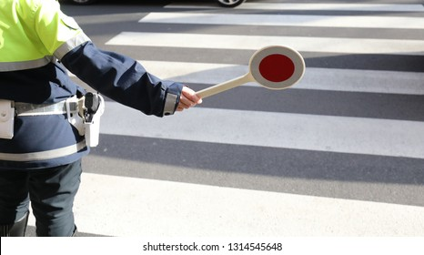 policeman with the paddle to stop the car on the pedestrian crossing