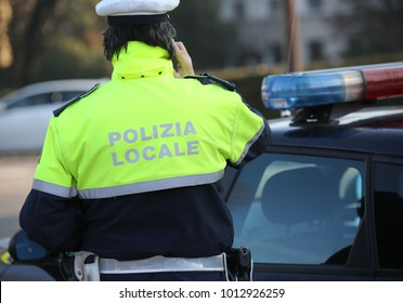 policeman is phoning near the police car in a city. The Text Polizia Locale means Local Police of the city in italian language
