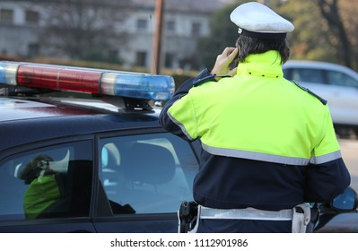 policeman talking on a cell phone in the street near his car