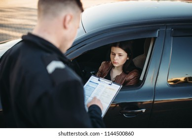 Policeman in uniform writes fine to female driver