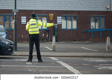 policeman wearing helmet and hi vis reflective jacket directs traffic on busy road
