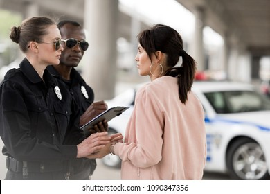 policewoman cheering up young woman while her partner writing in clipboard