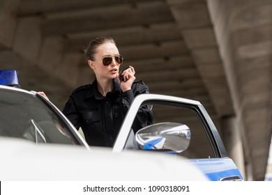 policewoman talking by radio set near police car