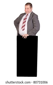 Policies with a friendly face behind the lectern isolated on white background. Jolly fat businessman holding a black panel. The fat man in a suit with face patronizing.