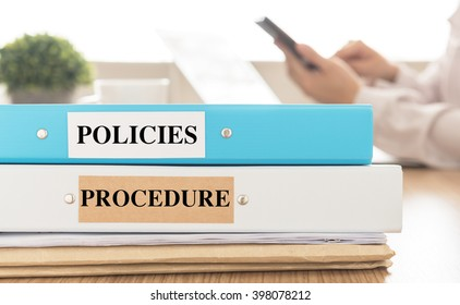 Policies and Procedures doucument place on desk in meeting room.  Policy, Procedure concept.