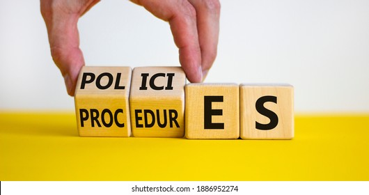 Policies vs procedures symbol. Male hand flips wooden cubes and changes the word 'procedures' to 'policies'. Beautiful yellow table, white background, copy space. Business and policies concept.