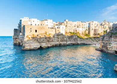 Polignano a Mare, beautiful and historical town on the seaside in Apulia region, southern Italy. White houses and buildings on top of a cliff overlooking the blue sea. Travel, architecture concepts