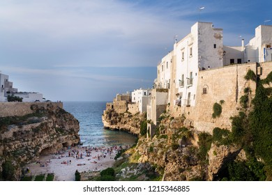 POLIGNANO A MARE, ITALY - JULY 6 2018: People on lovely beach Lama Monachile in Polignano a Mare, Adriatic Sea, Apulia, Bari province on July 6, 2018 in Polignano a Mare, Italy.