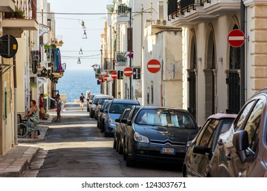 POLIGNANO A MARE, ITALY - JULY 6 2018: People walk along parked cars on street with many no entry traffic signs on July 6, 2018 in Polignano a Mare, Italy.