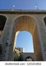 Polignano a Mare, Puglia, Italy - September 6, 2018: Arches of the Bourbon bridge seen from the bottom of Cala Monachile