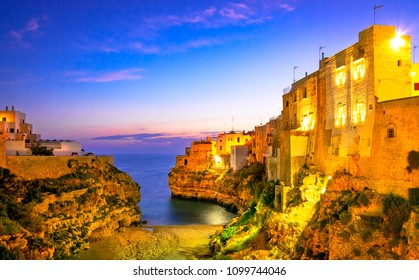 Polignano a Mare, Puglia, Italy: Sunrise at Cala Paura gulf with Bastione di Santo Stefano and Lama Monachile beach in background, Apulia, Italy, province of Bari