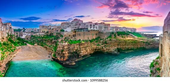 Polignano a Mare, Puglia, Italy: Sunset at Cala Paura gulf with Bastione di Santo Stefano and Lama Monachile beach in background, Apulia, Italy, province of Bari