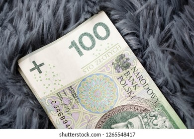 Polish banknotes 100 (PLN) and coins 1, 2 and 5 zloty close up.