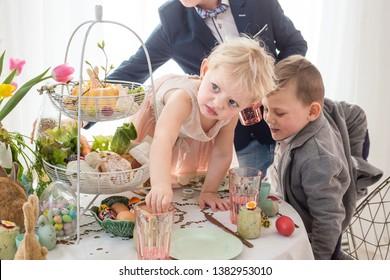 Polish children misbehaving, making a mess at Easter family table.