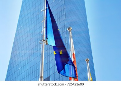 Polish and European union flags, flying and waving with glass wall office building background