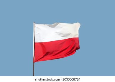Polish flag flying on flagpole on blue sky background