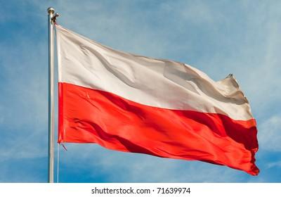 polish flag on a pole over beautiful sky