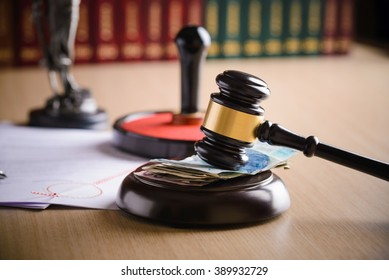 Polish money zloty  under the judge's gavel. Notary public stamper and notary act in the background. Bribe, corruption concept.
