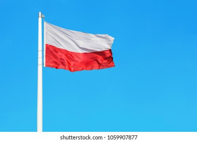 Polish national flag waving on the wind against clear blue sky